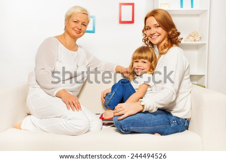 Family on sofa with mom girl and granny - stock photo