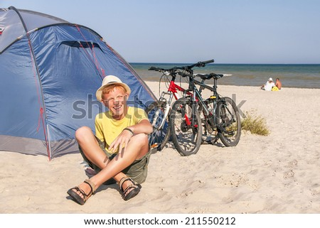 Family on the camping. Happy teenager is sitting near the tent with bicycles at the beach. Caucasian boy having fun and laughing. Active male model. Travel (vacations) and adventure concept. - stock photo