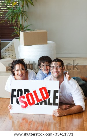 Family on the floor after buying new house with copy-space