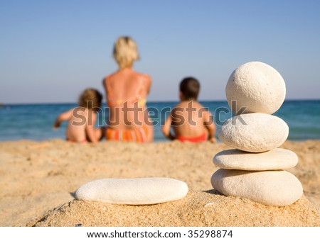 Family on the sunny beach looking to the sea framed by white pebbles - focus on the pebbles - stock photo