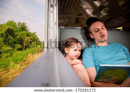 Family on the train reading a fairy tale book - stock photo