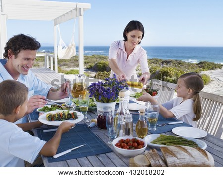 Family on vacation at beach having barbecue in summer - stock photo