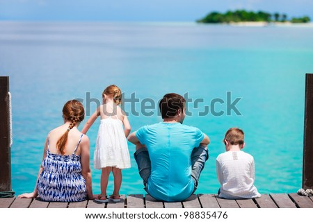 Family on wooden dock looking to ocean and tropical fishes - stock photo