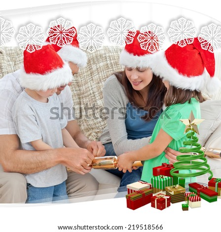 Family opening crackers together on the sofa against snowflake frame - stock photo
