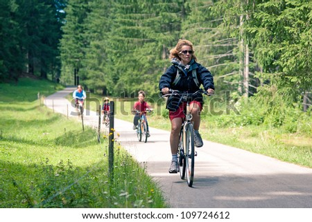 Family outdoors on bike. Bicycle path from St. Candid in italy t - stock photo