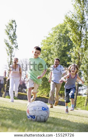 Family outdoors playing soccer and having fun - stock photo