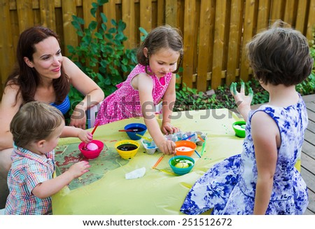 Family painting & decorating eggs outside in a springtime garden setting.  Mother smiles as girl shows her green dyed hand, while children have fun color dying their Easter eggs.  Part of a series.   - stock photo