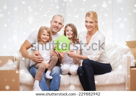 family, people, accommodation and ecology concept - smiling parents and two little girls moving into new home and waving hands over snowflakes background - stock photo