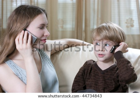 family phone talking - cute little boy and his mother are sitting on the sofa and talking by cell phone - stock photo