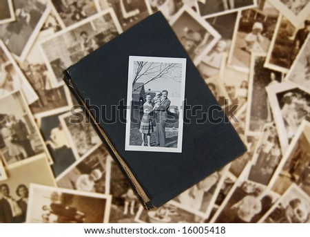 Family photo atop old book on pile of vintage photos - stock photo