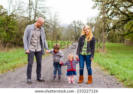 Family photo of a mother, father, and their two kids a boy and girl outdoors in the Fall. - stock photo
