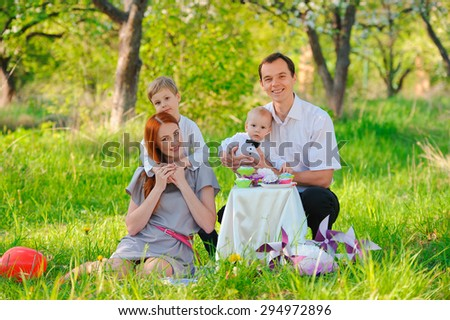 Family picnicking in the garden celebrates birthday