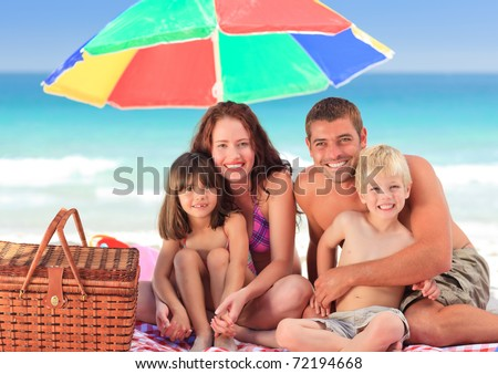 Family picnicking under a sol umbrella on the beach - stock photo