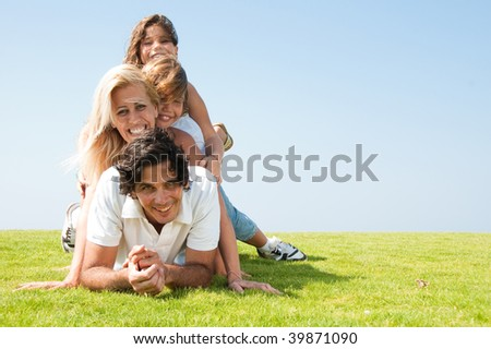 Family piled up on meadow and smiling at camera - stock photo