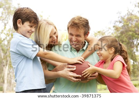 Family Playing American Football Together In Park - stock photo