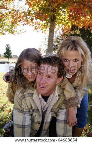 Family playing at the park in the fall laughing piggyback ride - stock photo