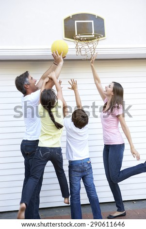 Family Playing Basketball Outside Garage - stock photo