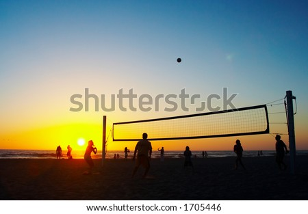 Family playing beach volleyball - stock photo