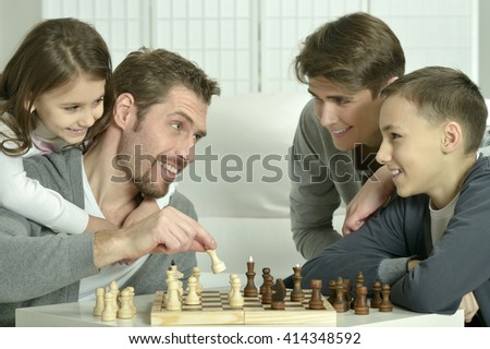 Family playing chess at home - stock photo