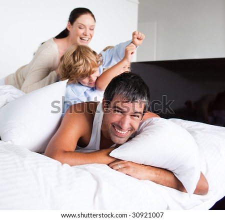 Family playing in bed - stock photo