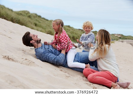 Family Playing In Sand Dunes Together - stock photo