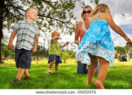 Family playing in the grass at a horse farm - stock photo