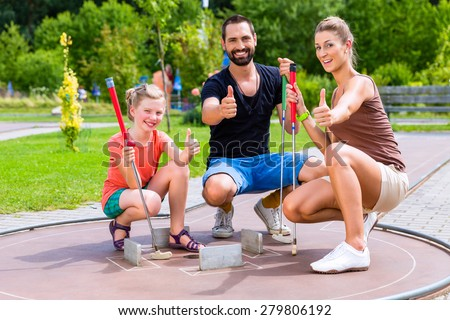 Family playing miniature golf on summer day - stock photo
