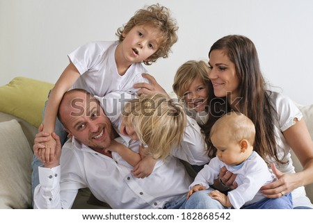 Family playing on sofa - children climbing on father