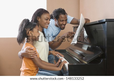 Family playing piano together - stock photo