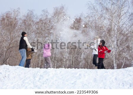 Family playing snowball. Parents with children walking at winter park