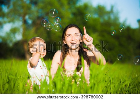 Family playing together outside. Mom and little daughter cheerfully catching soap bubbles. Portrait of happy joyful family of mum and child. - stock photo