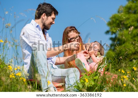 Family playing with wildflowers on meadow sitting in the grass