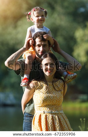 Family portrait. Daughter on dad's shoulders. In the background the lake. Photo.