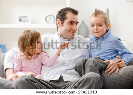 Family portrait, father and little siblings sitting together on couch, smiling.