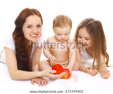 Family portrait, happy smiling mother and two children having fun together, baby sitting with red apple on a white background - stock photo