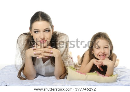 Family portrait, mother together with little daughter, lying on a white coverlet, fun smiling, white background. - stock photo