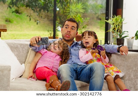 Family portrait of father and two daughters sitting together in sofa posing for selfie making funny faces. - stock photo