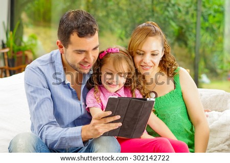 Family portrait of father, mother and two daughters sitting together in sofa playing happily with tablet. - stock photo