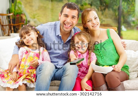 Family portrait of father, mother and two daughters sitting together in sofa smiling towards camera embracing each other. - stock photo