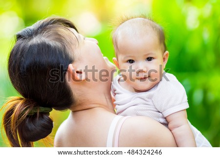 family portrait of 4 months baby feeling happy and smiles with her mother in the garden.