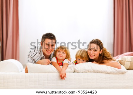 Family portrait of mother father and twins daughters on bed
