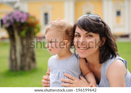 family portrait of smiling young woman and her daughter - stock photo
