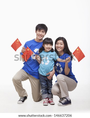 Family Portrait, one child with parents, waving Chinese flags, studio shot