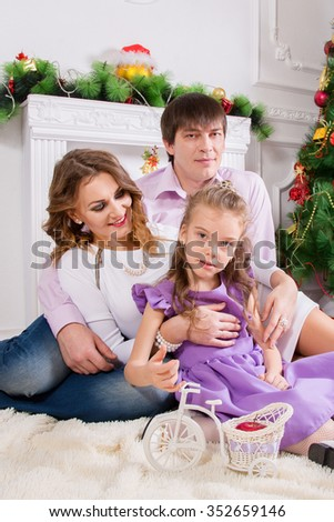 Family portrait with the child looking at the camera near a Christmas fir-tree. - stock photo
