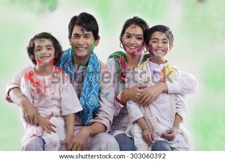 Family posing after playing holi - stock photo