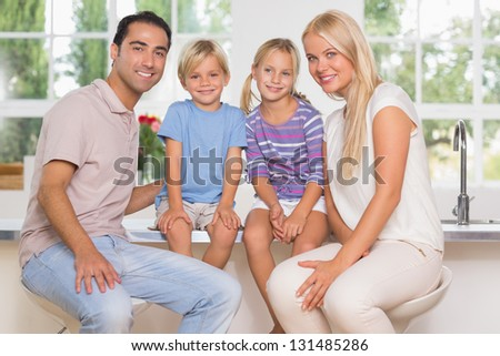 Family posing for a picture in the kitchen - stock photo