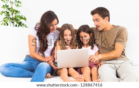 Family posing on a sofa with the laptop in the living room - stock photo