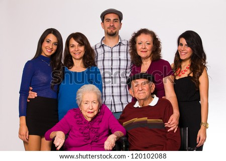 Family posing with elderly grandparents on a white background.