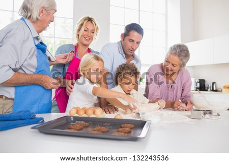 Family preparing biscuits together in the kitchen - stock photo