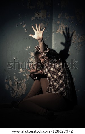 family problems and woman violence cover face fight fear. an insane psycho girl wearing a straight jacket. domestic violence. - stock photo